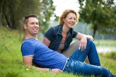 Cheerful couple sitting on grass outdoors Stock Images
