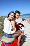 Cheerful couple sitting on moto by the beach Royalty Free Stock Photos