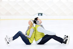 Cheerful couple sitting on the skating rink Stock Photo