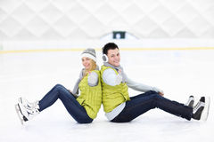 Cheerful couple sitting on the skating rink Stock Images