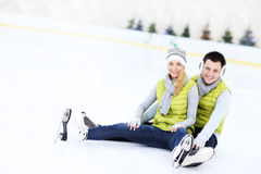 Cheerful couple sitting on the skating rink Royalty Free Stock Image