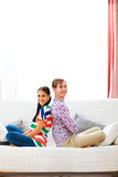 Cheerful couple sitting on sofa back to back Royalty Free Stock Images
