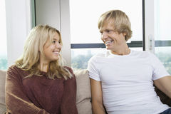 Cheerful couple sitting on sofa and looking at each other at home Stock Photo