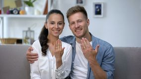Cheerful couple sitting on sofa, showing hands with engagement rings, love. Stock footage stock video