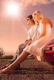 Cheerful couple sitting on their cabriolet car hood Stock Images