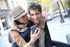 Cheerful couple with smartphone in city street Stock Images
