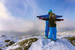 Cheerful couple snowboarders standing on the mountain and enjoye Stock Photos