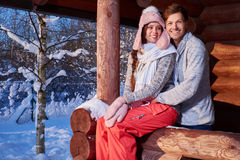 Cheerful couple spend winter holidays at mountain cottage Royalty Free Stock Images