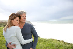 Cheerful couple standing by ocean stock photos