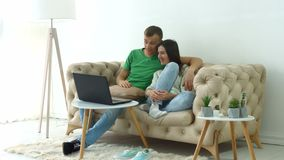 Cheerful couple streaming video online on laptop