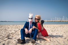 Cheerful couple are sunbathing on the beach. And enjoys vacation. Unusual men in elegant suit and comical mask with young women in bright red dress Stock Images