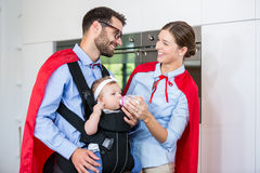 Cheerful couple in superhero costume feeding milk to daughter Stock Image