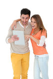 Cheerful couple with surprised look watching the tablet Stock Image