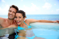Cheerful couple in swimming-pool Stock Photos
