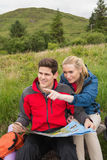 Cheerful couple taking a break on a hike to look at map with woman pointing Royalty Free Stock Photography