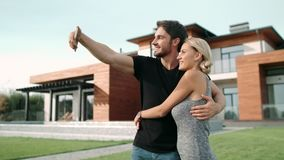 Cheerful couple taking selfie photo on mobile phone near luxury house. Handsome man taking mobile picture with blonde woman together. Young family posing for stock video