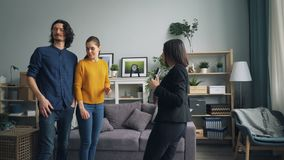 Cheerful couple talking to real estate agent looking at new apartment indoors