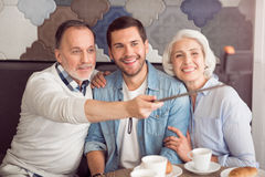 Cheerful couple and their grandson making selfies. Elated atmosphere. Joyful smiling senior couple and their adult son sitting at the table and making selfies Royalty Free Stock Photography