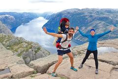 A cheerful couple and their little kid in the summit of the Pulpit Rock Preikestolen, Norway. stock photos