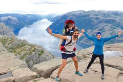 A cheerful couple and their little kid in the summit of the Pulpit Rock Preikestolen, Norway. stock images