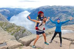 A cheerful couple and their little kid in the summit of the Pulpit Rock Preikestolen, Norway. royalty free stock image
