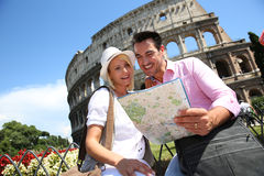 Cheerful couple traveling in Rome. Tourists reading map in front of the Coliseum, Rome Stock Image