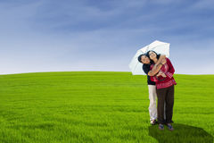 Cheerful couple with umbrella on green field Royalty Free Stock Images