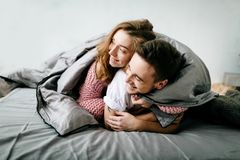 Cheerful couple under the coverlet in their bed. Artwork. Soft focus on the girl. Cheerful couple under the coverlet in their bed. A couple in love having fun in stock photography