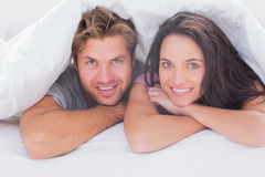Cheerful couple under the duvet Royalty Free Stock Photos