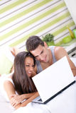 Cheerful couple using a computer Stock Photos