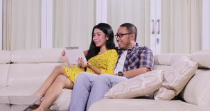 Cheerful couple using digital tablet on couch. Cheerful couple using digital tablet together while sitting on the couch in the living room at home. Shot in 4k stock video footage