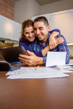 Cheerful couple using digital tablet at kitchen Stock Images