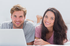 Cheerful couple using laptop in bed Stock Photo