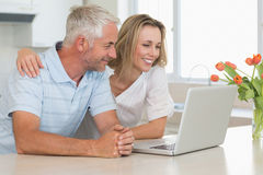 Cheerful couple using laptop together at the worktop Stock Photography
