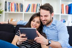 Cheerful couple using a tablet on line sitting in the living room at home stock images
