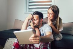 Couple using a tablet online sitting in the living room at home royalty free stock images