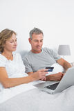 Cheerful couple using their laptop to buy online Royalty Free Stock Image