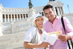 Cheerful couple visiting Rome with help of map. Couple reading map by the monument of Victor Emmanuel II Stock Photography