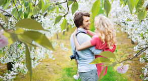 Cheerful couple walking among apple-trees Stock Image