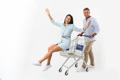 Cheerful couple walking with a shopping cart. At the supermarket, happy women sitting in a trolley away isolated Royalty Free Stock Photo