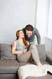 Cheerful couple watching photos on internet with tablet Stock Image