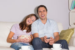 Cheerful couple watching TV with popcorn bowl on sofa at home Royalty Free Stock Images