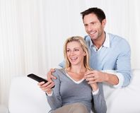 Cheerful couple watching tv Stock Photos