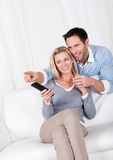 Cheerful couple watching tv Stock Images