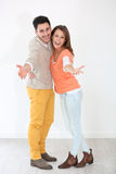 Cheerful couple on white background. Cheerful couple spreading arms towards camera Royalty Free Stock Photography