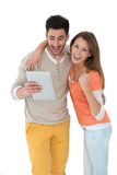 Cheerful couple on white background with tablet Royalty Free Stock Photography