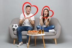 Cheerful couple woman man football fans cheer up support favorite team, sitting holding big red wooden hearts isolated. Cheerful couple women men football fans royalty free stock photo
