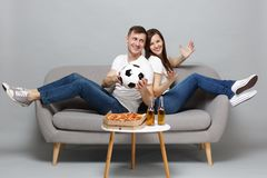 Cheerful couple woman man football fans cheer up support favorite team with soccer ball, sitting back to back isolated. Cheerful couple women men football fans stock photos