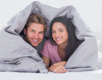 Cheerful couple wrapped in the duvet Stock Image