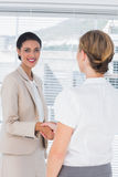 Cheerful coworkers shaking hands Stock Photos